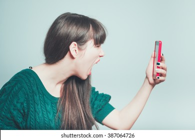 Portrait of a young woman shouting at a mobile phone, isolated on a gray background