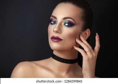 Portrait of a young woman showing a bright, confident, attractive image and bold rich makeup.