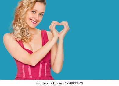 portrait of young woman showing heart symbol on blue color background