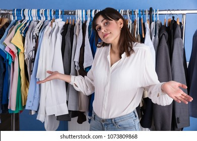 Portrait Of A Young Woman Shrugging In Front Of Clothes Rail
