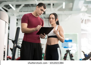 Portrait of young woman signing contract with personal fitness coach in modern gym, copy space
