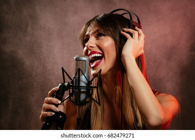 Portrait of a young woman singer with headphones in front of the microphone. Sing with mouth wide open and with an expression of happiness on her face.