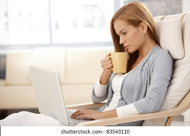 Portrait of young woman sitting in armchair with laptop computer, drinking tea, looking at screen.?
