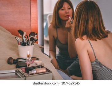 Portrait of young woman sitting in front of mirror doing make-up. Paints her lips with lipstick.
