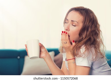 Portrait of a young woman sitting on sofa with cup of coffee and yawning