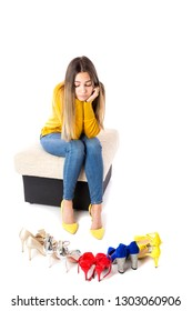 Portrait of a young woman sitting on the sofa and choosing  shoes against white. Consumerism concept