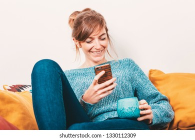 portrait of young woman sitting on a sofa, watching at mobile phone and smiling - chill out concept - wireless communication concept