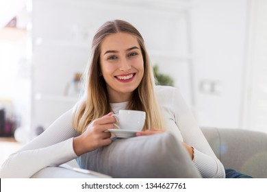 Portrait of a young woman sitting on sofa with cup of coffee