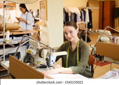 Portrait of young woman sitting at the table and using sewing machine in her work in atelier