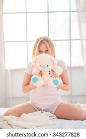 Portrait of a young woman sitting with teddy bear on the bed at home