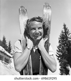 Portrait of young woman with skis