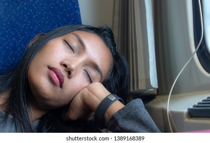 The portrait of young woman sleeping on a train by the window. A tired passenger relaxes in a driving train behind the window.