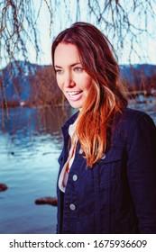 Porträt einer jungen Frau mit leicht geöffneter Bluse und Jeans-Jacke an einem See.