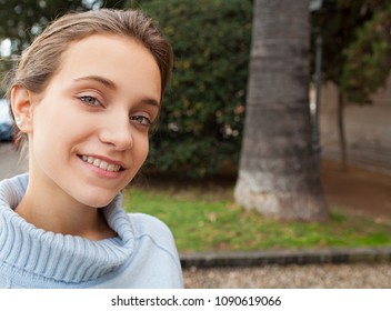 Portrait of young woman smiling looking  visiting a park, relaxing leisure recreation. Healthy positive teenager female, smart wellbeing lifestyle, outdoors. Friendly cute fresh youth, joyful face.