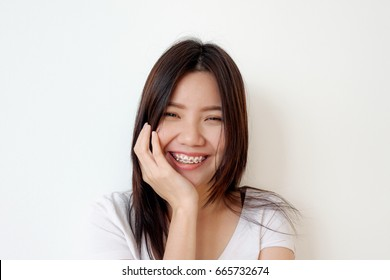 Portrait of a young woman smiling with pink braces, white background, Happy concept, Asian