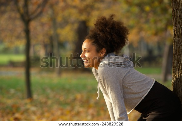Portrait of a young woman smiling and resting after workout in the park