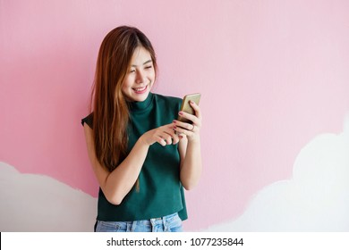 Portrait of Young Woman Smiling while using Smart Phone at the wall. Lifestyle of Modern Female