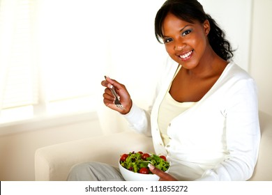 Portrait of a young woman smiling at you while eating healthy green salad at home indoor. With copyspace