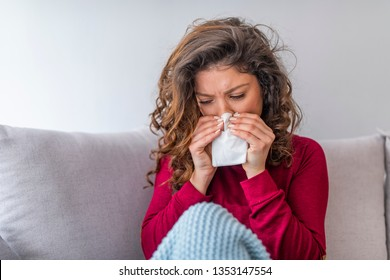 Portrait of a young woman sneezing in to tissue. Sick Woman. Flu. Woman Caught Cold. Young Woman Infected With Cold Blowing Her Nose In Handkerchief. Sick girl with a headache sitting on a sofa