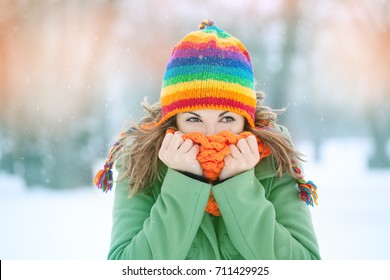 Portrait of a young woman in snow  with scarf on her face trying to warm herself. Winter concept