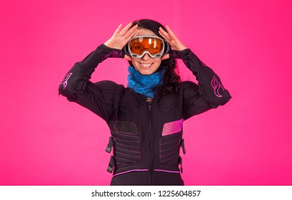 Portrait young woman in a snowboarder clothes and wearing a protective mask glasses on a pink background.
