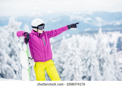 Portrait of a young woman snowboarder pointing with hand standing outdoors on the snowy mountains