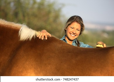 Portrait of young woman standing behind horse, brushing, looking at camera, smiling.