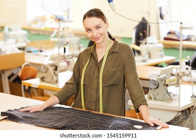 Portrait of young woman standing near her workplace with fabric and looking at camera in workshop