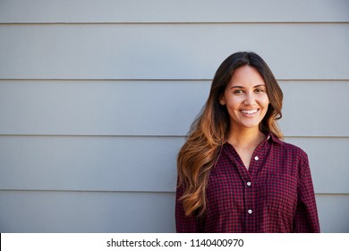 Portrait Of Young Woman Standing Outside Grey Clapboard House