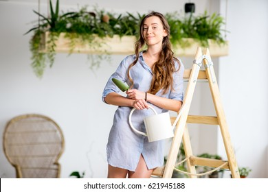 Portrait of a young woman standing with watering can on the ladder at home or oranery with green plants