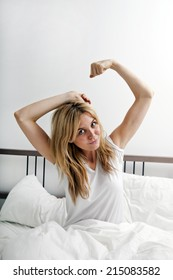Portrait of young woman stretching in bed