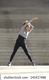 Portrait of a young woman stretching exercise outdoors