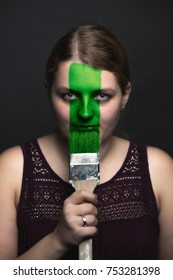 Portrait of a young woman stroking a brush across her face
