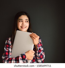 Portrait of a young woman student holding a computer.Back to school education knowledge college university concept.University girl used computer on black background.Education and technology concept.