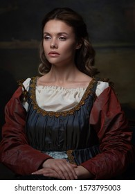 Portrait of a young woman in the style of a Renaissance painting. Beautiful mysterious girl in medieval dress