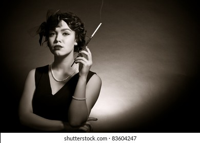 Portrait of the young woman in style of a retro against a dark background