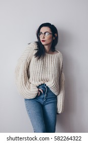 Portrait of young woman in stylish oversized sweater and mom jeans