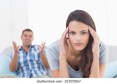 Portrait of young woman suffering from headache while man arguing at home