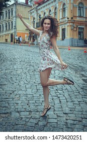 Portrait of a young woman in the summer rain, she frolics on the street.