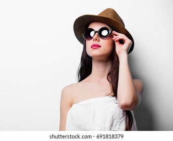 portrait of the young woman with sunglasses and hat on white background