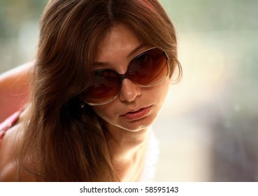 Portrait of young woman with sunglasses, window background