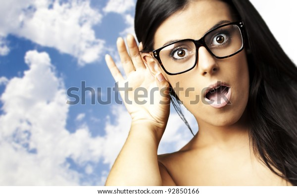 portrait of young woman surprised hearing a sound against a cloudy sky background