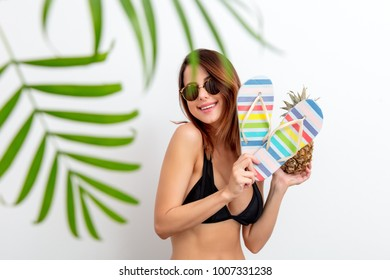 26f0dbdfca26a Portrait of young woman in swimsuit and sunglasses with pineapple and flip  flops shoes on white