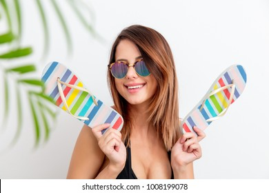 Portrait of young woman in swimsuit and sunglasses with flip flops shoes on white background. Summer season image concept
