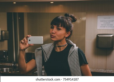 Portrait of young woman takes a selfie with mobile phone in the toilet in front of the mirror
