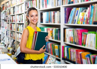 Portrait young woman taking literature books in store with prints
