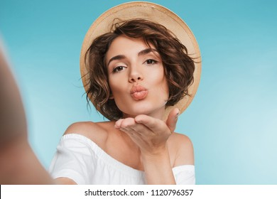 Portrait of a young woman taking a selfie and sending kiss isolated over blue background