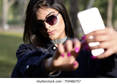 Portrait of a young woman taking a selfie with a smartphone