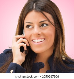 Portrait Of A Young Woman Talking On Cellphone against a pink background