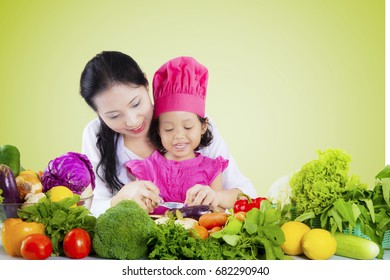 Portrait of a young woman teaching her daughter to prepare and cut vegetables, shot with green screen background